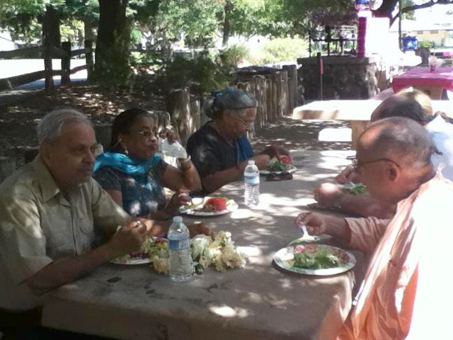 janmastami-ponderosa-park-01 Srila Janardan Maharaj conversing with guests while honoring prasadam